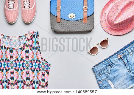 Street style Fashion girl clothes accessories set. Hipster woman, trendy handbag, top, denim, gumshoes, pink hat and sunglasses. Bright urban creative outfit. Overhead, top view on gray background