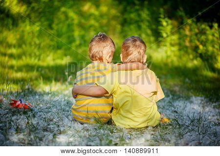 Two little boys friends hug each other in summer garden. Brother love. Concept friendship. Back view.