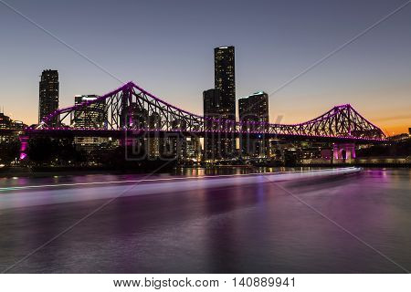 BRISBANE, AUSTRALIA: Story Bridge and cityscape by sunset, with CityCat ferry light trails on the river - magenta lights