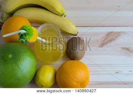 Fresh exotic fruits and juice in glass jug on wooden background