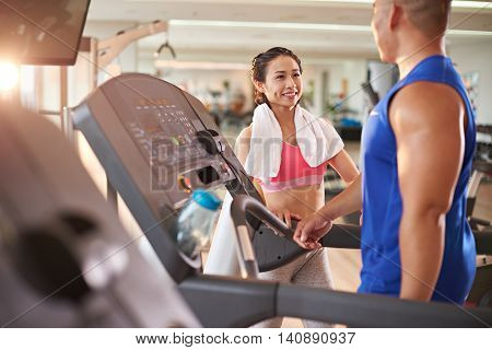 Young Asian woman flirting with sportsman in gym