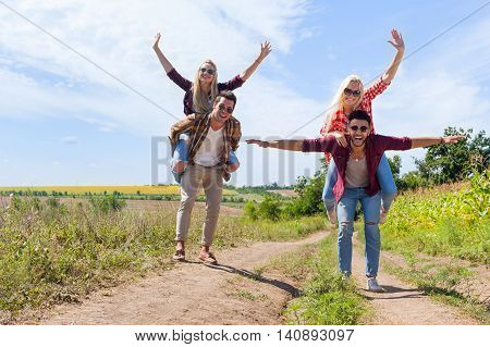 Two men girlfriends piggyback rides cheerful couple young friends summer sunny day young people group countryside road happy smile