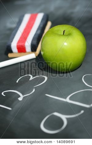 Green apple on chalkboard with easer