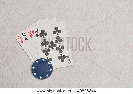 The different suit of the number 9 cards in a deck of cards displayed on a white background with a blue poker chip