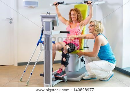 Patient in exercise machine and orthopedic brace getting help with leg rehabilitation from instructor kneeling down next to her