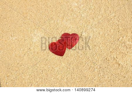 Two red hearts on the sand close up shoot