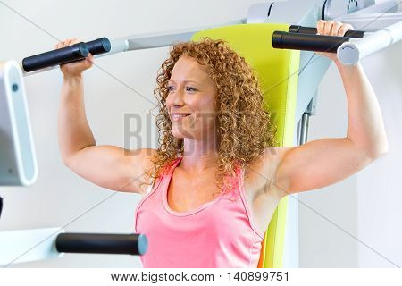 Smiling fit woman with curly hair with arms in the raised position with shoulder strengthening machine