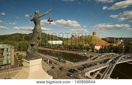 AERIAL. In front - statue on top of the Electricity building Old town of Vilnius in the background. Vilnius Lithuania.