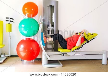 Side view on single senior woman doing leg strengthening exercises in gym with stability balls nearby