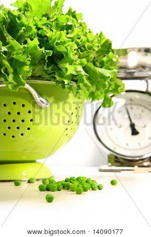 Fresh lettuce in strainer against white background
