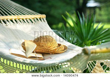 Hängematte, Buch, Hut und Brille an einem sonnigen Sommertag