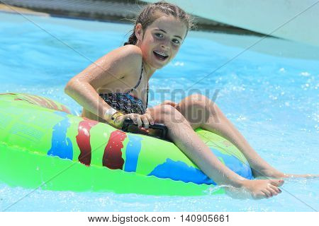 Rhodes Greece-July 30 2016: The girl after rafting slide in the Water park.Rafting slide is one of many popular game for adults and children in park.Water Water Park is located on the island of Rhodes in Greece and one of the largest in Europe