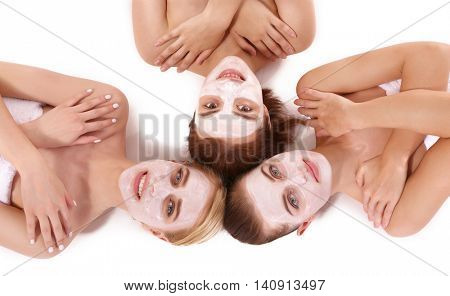 Young beautiful women relaxing with facial masks, top view