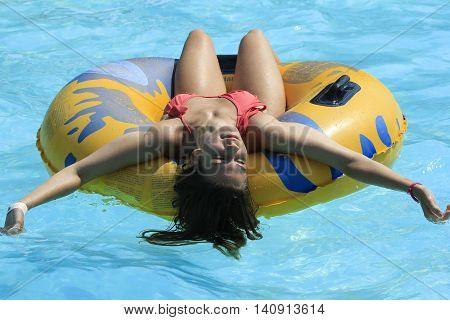 Rhodes Greece-July 31,2016:The girl joying after rafting slide in the Water park.Rafting slide is one of many popular game for adults and children in park.Water Park is located on the island of Rhodes in Greece and one of the most largest in Europe