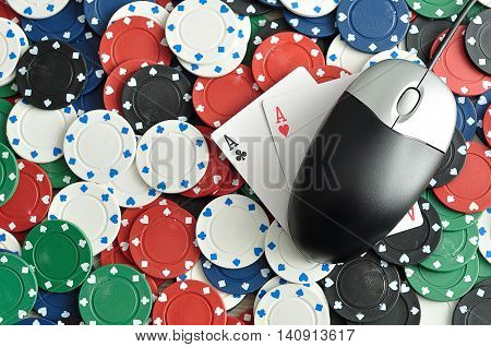 A computer mouse with poker chips and 2 ace cards symbolizing on line poker