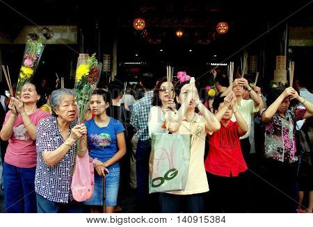 Singapore - December 13 2007: Faithful Buddhist women praying with incense sticks and floral offerings at the Kuan Im Thong Hood Cho Chinese Temple on Albert Mall