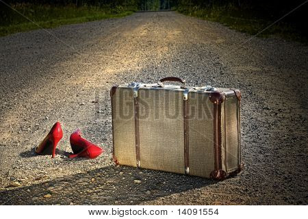 Old suitcase with red shoes left on dirt road