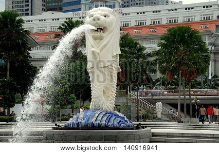 Singapore - December 12 2007: The Merlion Fountain at Marina Bay with the adjacent Fullerton Hotel