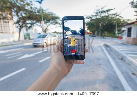 California, United States - July 30, 2016: Close up of a man holding a unbranded smartphone while playing Pokemon Go game