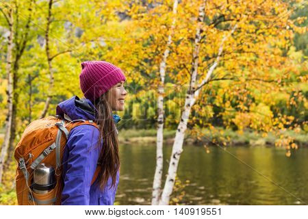 Woman hiker hiking looking at scenic view of fall foliage mountain landscape . Adventure travel outdoors person standing relaxing near river during nature hike in autumn season.
