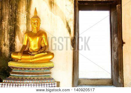 Golden meditating buddha next to opening door at Wat Phutthaisawan Ayutthaya Thailand