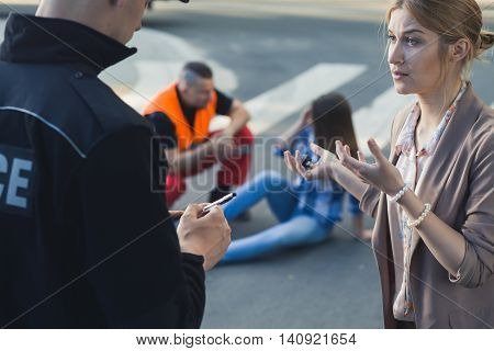 Woman talking with the police officer with the casualty of car accident at the background poster