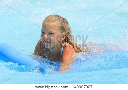 Rhodes Greece-July 31 2016:The girl joying after mat racer slide.Mat racer slide is very popular for young people in the Water Park.
