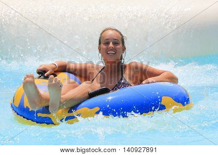 Rhodes Greece-July 31 2016:The girl joying in the pool after rafting slide in the Water park.Rafting slide is one of many popular game for adults and children in park.Water Park is located on the island of Rhodes in Greece and one of the must popular