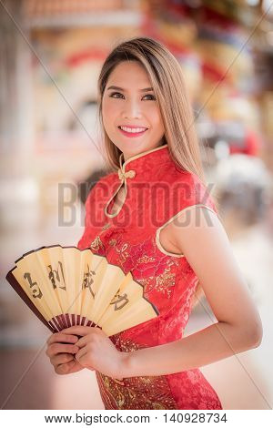 The Asian Woman In Chinese Dress Holding Couplet 'success' (chinese Word) With Chinese Temple Backgr