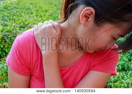 Woman neck pain or shoulder pain in garden concept.