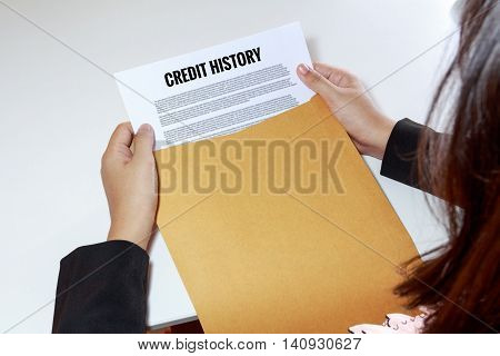 Woman hands holding credit history document in envelope - business concept