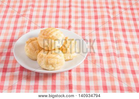 Eclair cream dessert in a dish on red and white chintz background.