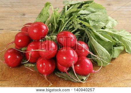bunch of fresh homegrown organic radish on a wooden board