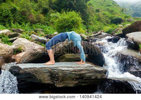 Yoga outdoors - young sporty fit woman doing Ashtanga Vinyasa Yoga asana Urdhva Dhanurasana  - upward bow pose at tropical waterfall