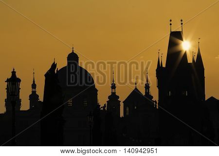 Golden silhouette of the Prague Charles Bridge and towers and churches with dazzle sun ray over the bridge tower. Magical picture of the Czech capital city Old Town Prague.