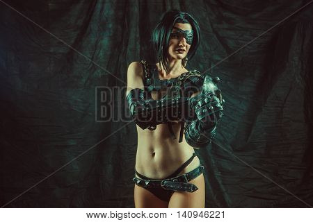 Powerful One-eyed Steam Punk Woman In Metal Lingerie Is Showing Obscene Gesture To The Camera.