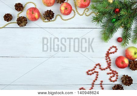 Christmas background in rustic style. Top view. New Year background with fir-tree beads apples balls and fir-cones on wooden background. / Christmas card with christmas natural decorations/.
