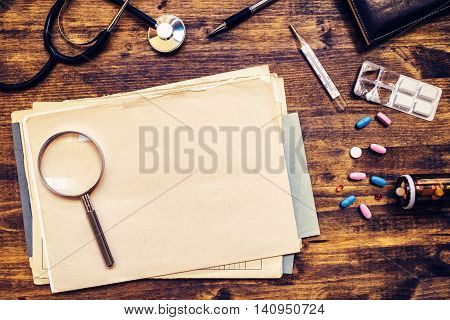 General medical practitioner work desk as copy space. Doctor's workspace with assorted office supplies such as stethoscope loupe thermometer pencil tablets and pills top view. poster