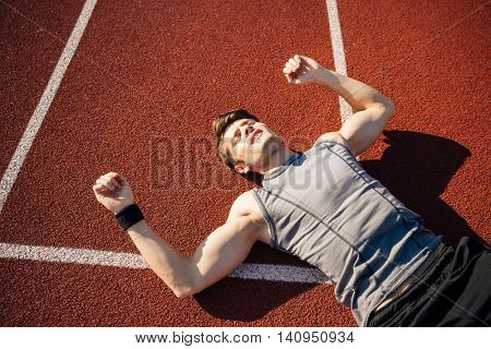 Fitness young man laying on running track after hard workout at the stadium