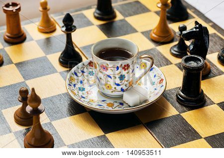 Tactic and strategy of modern life in concept. Cup of coffee on chessboard with wooden figure arond.