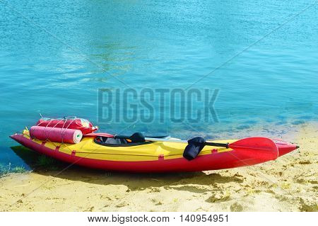 kayak with an oar stands on the sandy shore of the pond