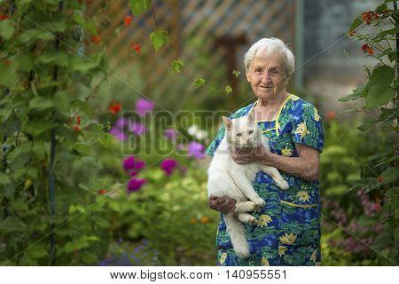 Elderly woman in garden with cat on hands.