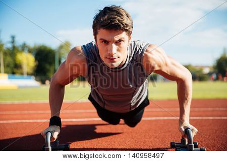 Young male athlete makes push ups on a racetrack at the stadium
