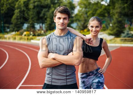 Full length shot of young man and woman standing on athletics race track at the stadium