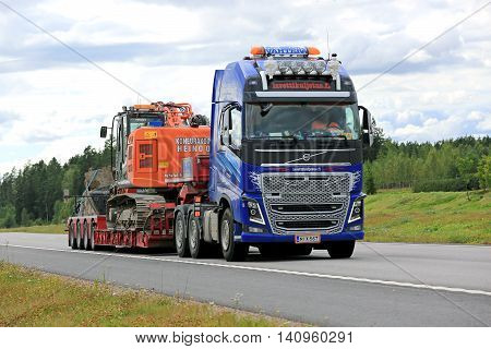 PAIMIO, FINLAND - JULY 31, 2016: Volvo FH16 600 hauls Hitachi tracked excavator on Noteboom trailer along freeway in South of Finland.