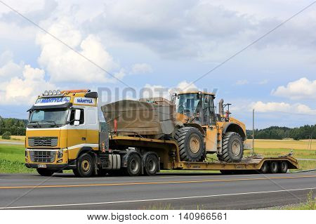 SALO, FINLAND - JULY 30, 2016: Yellow Volvo FH16 semi of Mantyla E & E in heavy equipment haul stops for by road in South of Finland. The truck transports Cat 980H wheel loader on drop deck trailer.