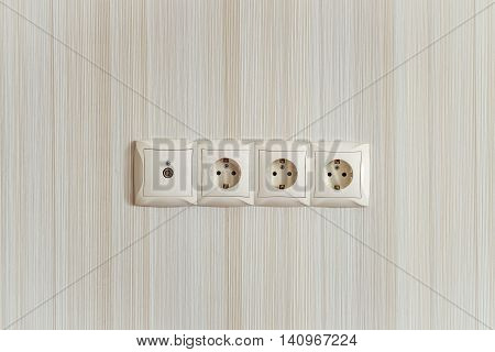 Electric socket strip with TV output. Interlocked electrical outlet on the wall.