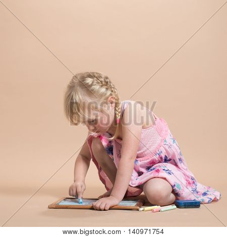Little girl engrossed in play with her colorful chalks and blackboard