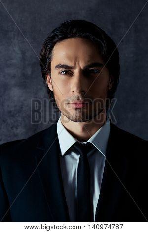 Portrait Of Handsome Harsh Hispanic Man On Gray Background