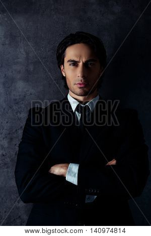 Portrait Of Harsh Young Man In Formalwear Crossing Arms